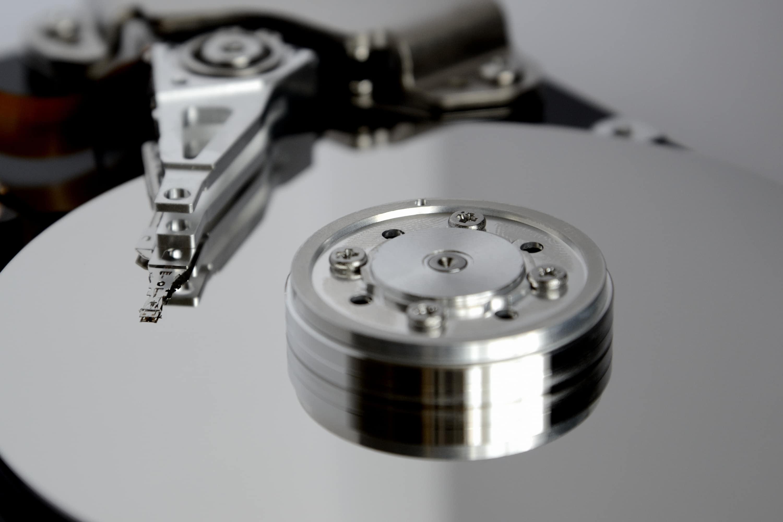 eine offene magnetische Festplatte, man sieht die Scheiben und den Lesekopf