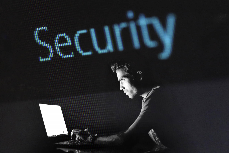 ein Daumenfinger Abdruck, im Hintergrund verschwommen ein Mann; Schriftzug Security