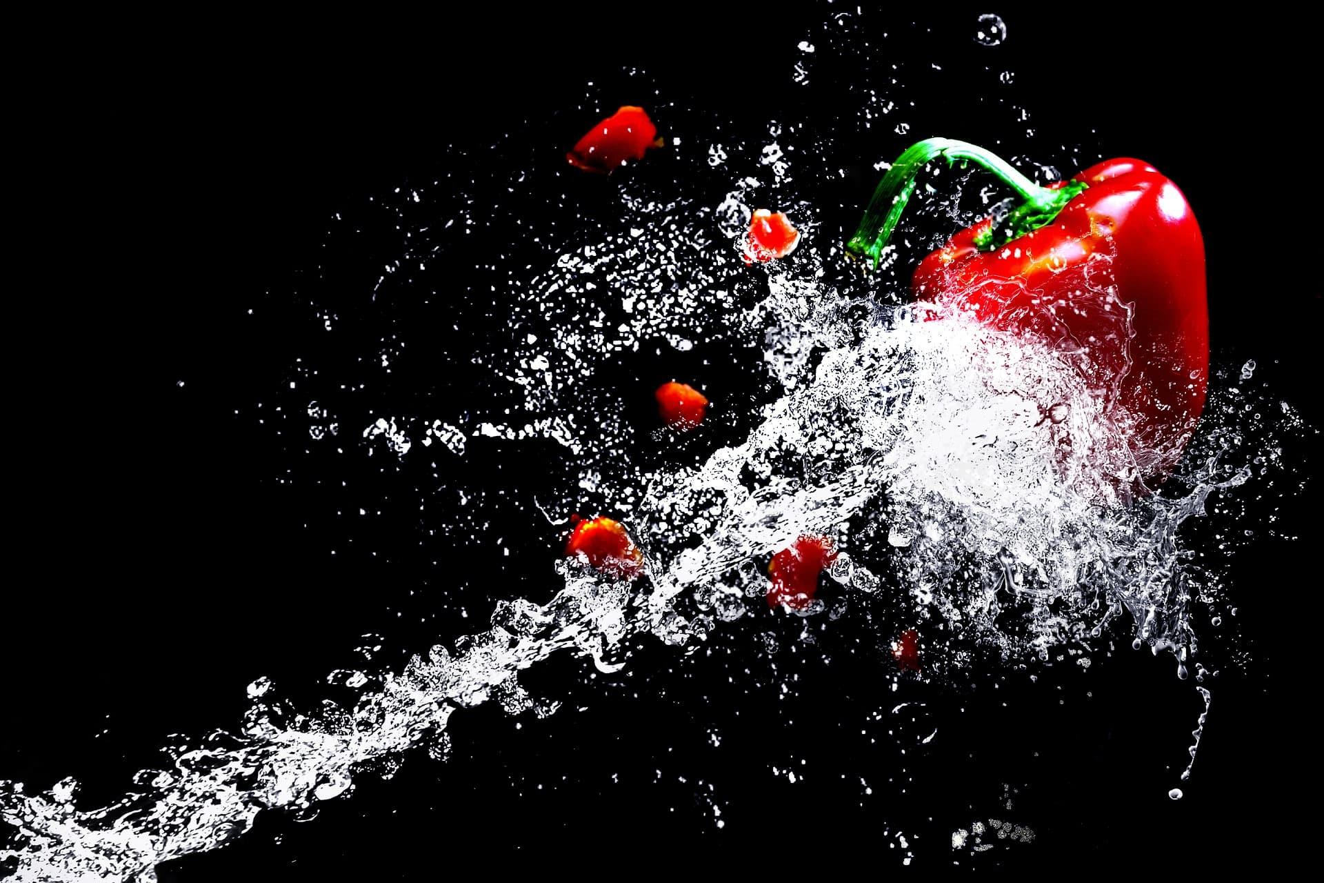 eine Hochgeschwindigkeitsaufnahme; ein Wasserstrahl spritzt auf eine rote Paprika