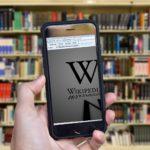 Handy mit aufgerufener Wikipedia Seite im Vordergrund. Im Hintergrund ein gut gefülltes Bücherregal.